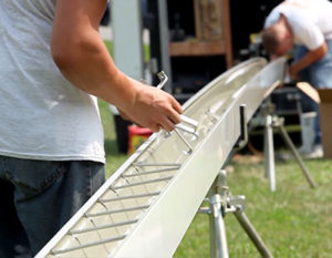 Brackets Being Inserted By Gutter Installer Into Extruded Seamless Gutters